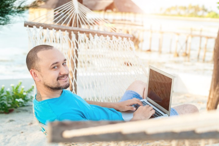 young man with laptop on vacation S4WJVS8